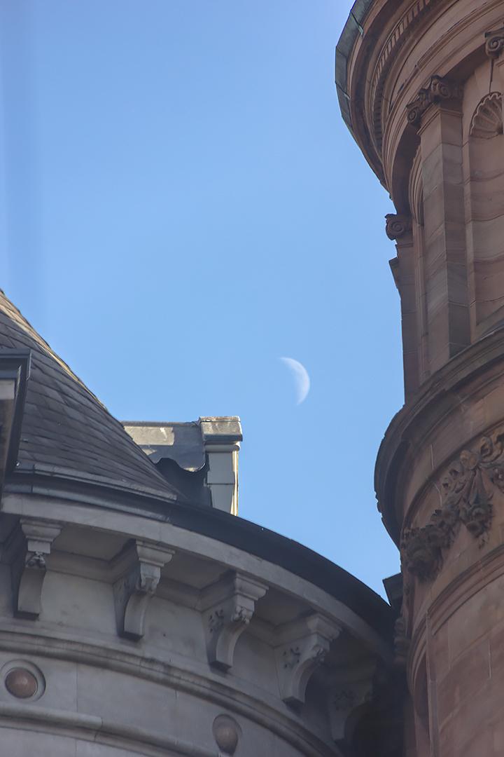 The moon between buildings in Dublin
